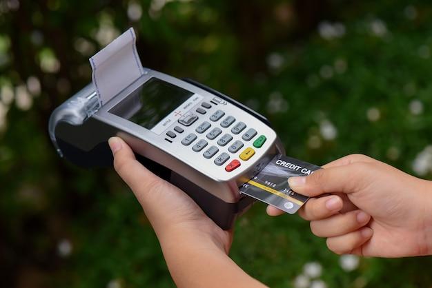Conceito de pagamento com cartão de crédito. close-up mão inserir cartão de crédito mock up com cartão em branco com uma máquina de furto de cartão Foto Premium