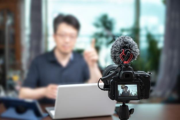 Conceito de palestra on-line. homem de meia idade asiático dando palestras on-line em casa. Foto Premium