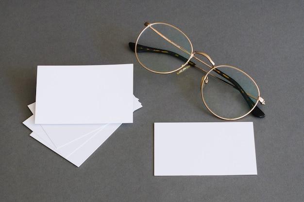 Conceito de papelaria com cartões de visita e óculos Foto Premium