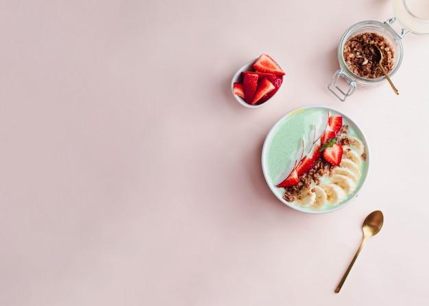 Conceito de pequeno-almoço saudável. tigela de granola de grãos inteiros com iogurte de morango, banana e hortelã no fundo rosa. conceito probiótico. flatlay com copyspace Foto Premium