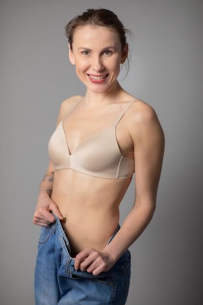Conceito de perda de peso. jovem mostra sua perda de peso e vestindo seus jeans velhos. mulher magro em jeans grandes mostrando como ela estava perdendo peso Foto Premium