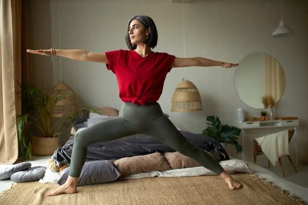 Conceito de pessoas, atividade, saúde e vitalidade. mulher jovem descalça fazendo exercícios em casa e praticando ioga de fluxo de vinyasa no quarto Foto gratuita