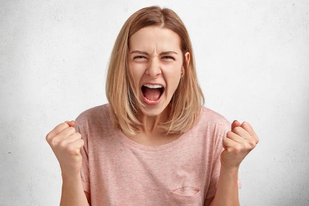 Conceito de pessoas e agressão. jovem modelo irritada com penteado curto, vestida com roupas casuais, fecha os punhos de raiva, briga com o marido Foto gratuita