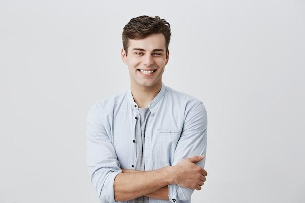 Conceito de pessoas e estilo de vida. homem caucasiano jovem atraente de bom humor, camisa azul de mangas compridas, sorrindo alegremente mostrando os dentes brancos perfeitos, felizes com notícias positivas, mantendo os braços cruzados. Foto gratuita