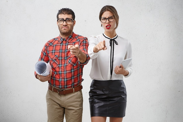 Conceito de pessoas, emoções e trabalho. jovem barbudo descontente com óculos quadrados e mulher com expressão atraente Foto gratuita