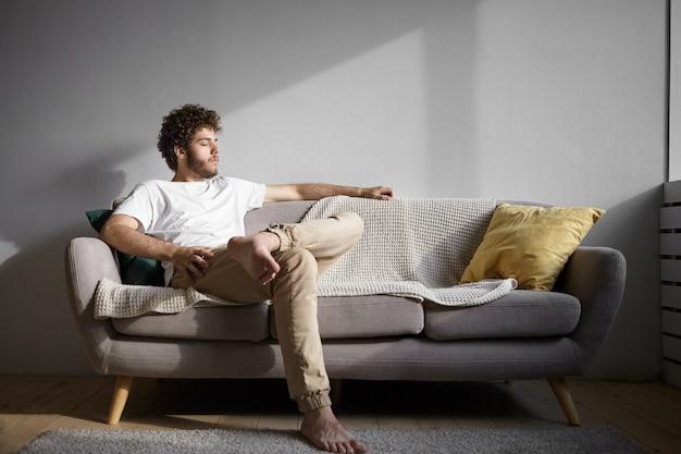 Conceito de pessoas, estilo de vida, descanso e relaxamento. foto de um cara bonito com os pés descalços, descansando dentro de casa, sentado no sofá confortável e fechando os olhos. jovem elegante com barba por fazer relaxando sozinho em casa Foto gratuita