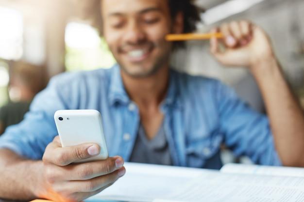 Conceito de pessoas, estilo de vida, tecnologia e comunicação. estudante do sexo masculino, barbudo e bonito, de pele escura, vestindo camisa azul, usando o celular, navegando no feed de notícias nas redes sociais, rindo de memes Foto gratuita