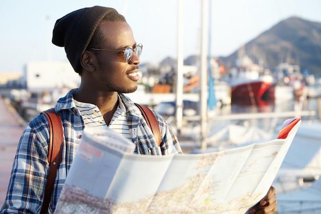 Conceito de pessoas, estilo de vida, viagens e aventuras. homem no cais, rodeado de iates e navios em elegantes óculos de sol de chapéu e espelho, segurando o guia de papel, olhando de lado no mar com um sorriso satisfeito Foto gratuita