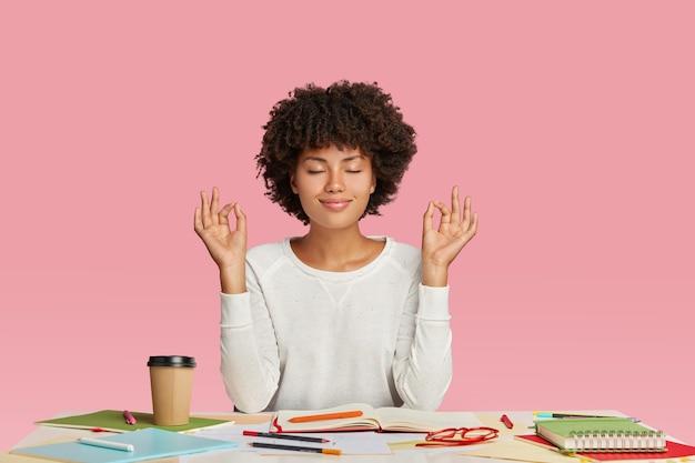 Conceito de pessoas, harmonia e trabalho. mulher de pele escura satisfeita com corte de cabelo afro, medita na área de trabalho, mantém os olhos fechados Foto gratuita