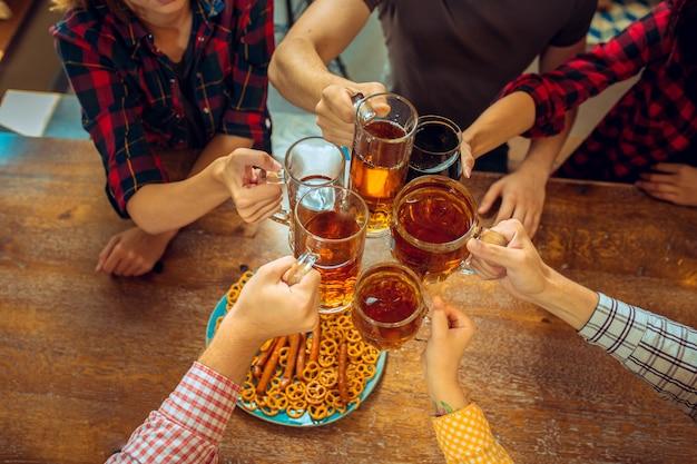 Conceito de pessoas, lazer, amizade e comunicação - amigos felizes bebendo cerveja, conversando e tilintar de copos no bar ou pub Foto gratuita