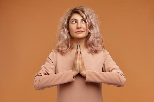 Conceito de pessoas, paz, meditação e zen. foto de mulher jovem e elegante com piercing no nariz e cabelo encaracolado de mãos dadas em namastê, meditando Foto gratuita