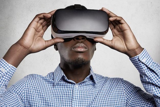 Conceito de pessoas, tecnologia, ciberespaço e entretenimento. homem africano vestido com camisa quadriculada usando fone de ouvido 3d, jogando videogame. Foto gratuita