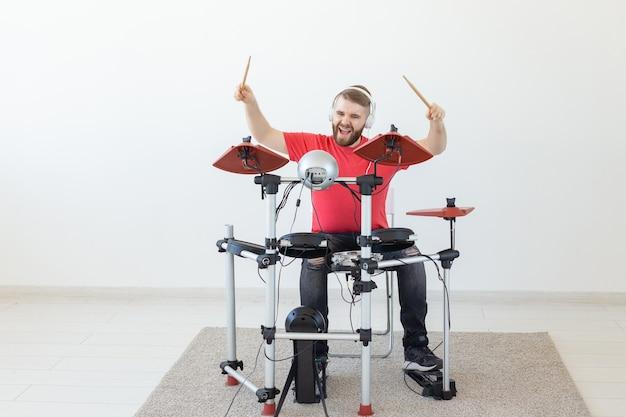 Conceito de pessoas, tempo livre e hobby - baterista masculino legal sobre fundo de sala Foto Premium