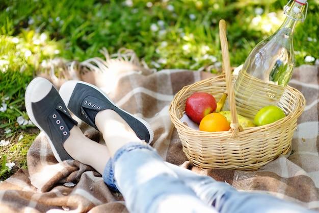 Conceito de piquenique de primavera. cesta de piquenique com frutas, flores e água no frasco de vidro Foto Premium