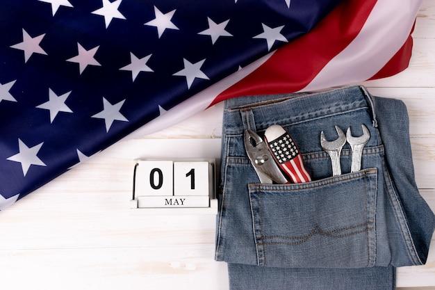Conceito de plano de fundo do dia do trabalho - jeans, muitas ferramentas úteis com a bandeira do eua Foto Premium