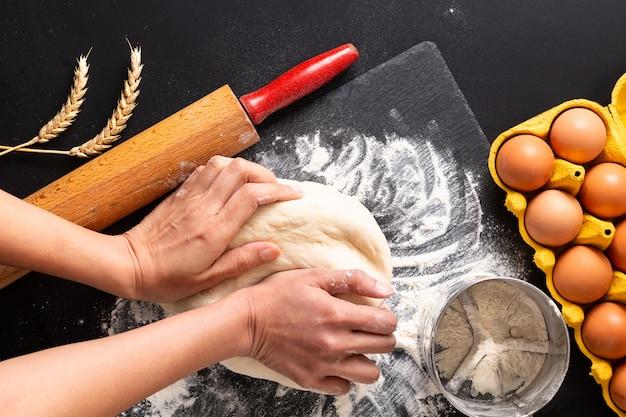 Conceito de preparação de alimentos sobre a cabeça tiro amassar a massa para padaria, pizza ou massas em fundo preto com espaço de cópia Foto Premium