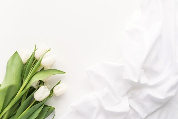 Conceito de primavera. buquê de tulipa branca e tecido para simulação de design em fundo branco com espaço de cópia Foto Premium