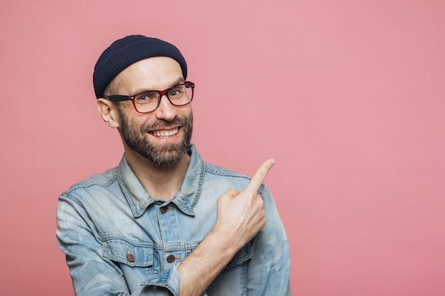 Conceito de propaganda. jovem barbudo alegre com expressão feliz usa óculos Foto Premium
