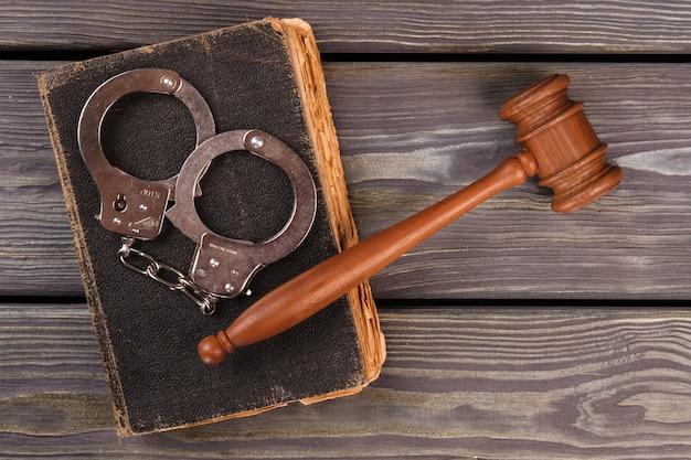 Conceito de punição e prisão. martelo de madeira com algemas e livro velho e gasto. antigo fundo de mesa. Foto Premium