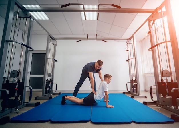 Conceito de reabilitação. jovem rapaz fazendo exercícios na esteira sob a supervisão do fisioterapeuta Foto Premium