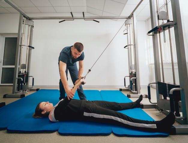 Conceito de reabilitação. mulher jovem e bonita fazendo exercícios na esteira, sob a supervisão do fisioterapeuta Foto Premium