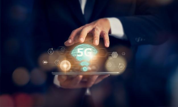 Conceito de rede futura tecnologia 5g, mãos de empresário segurando o tablet e interface de tela de redes de alta velocidade nova geração. sistemas sem fio e internet das coisas (iot). Foto Premium