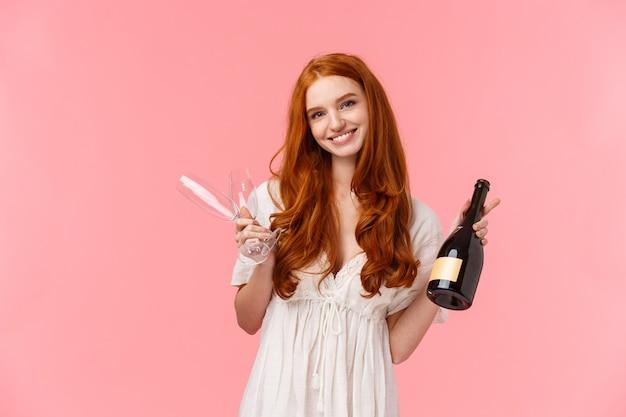 Conceito de relacionamento, celebração e ternura. linda garota caucasiana com cabelo longo encaracolado vermelho em vestido branco, convidando para beber juntos, segurando champanhe e duas taças, sorrindo Foto Premium