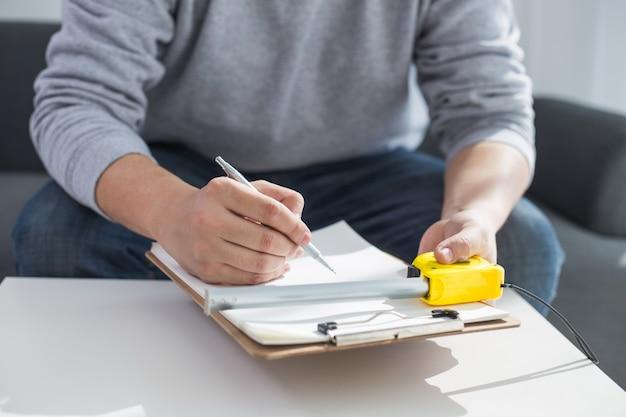 Conceito de reparação, construção e habitação - close up of male hands writing in clipboard Foto gratuita