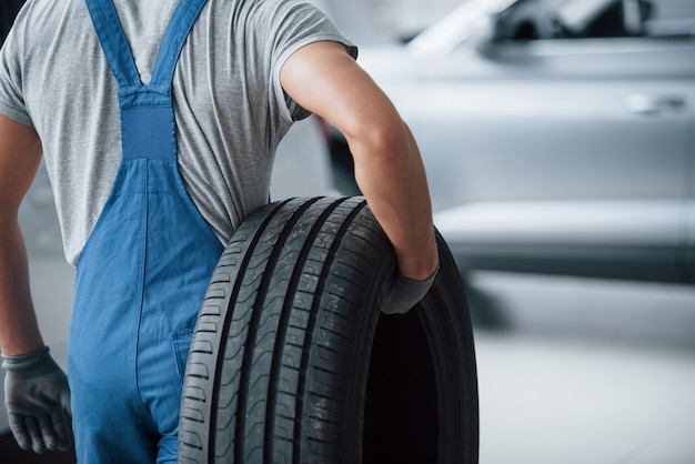 Conceito de reparo. mecânico segurando um pneu na oficina. substituição de pneus de inverno e verão Foto gratuita