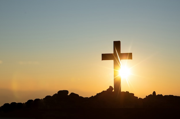 Conceito de ressurreição: crucificação de jesus cristo cruz ao pôr do sol Foto gratuita
