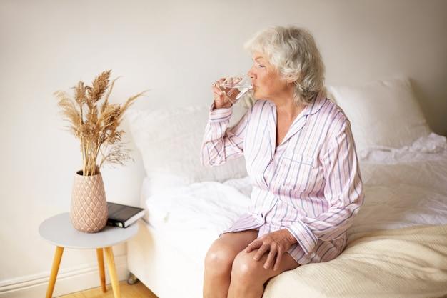 Conceito de rituais matinais, lesiure, descanso e hora de dormir. atraente aposentada com cabelos grisalhos sentada na cama em um interior aconchegante, segurando uma caneca, bebendo água para fazer seu sistema digestivo funcionar Foto gratuita