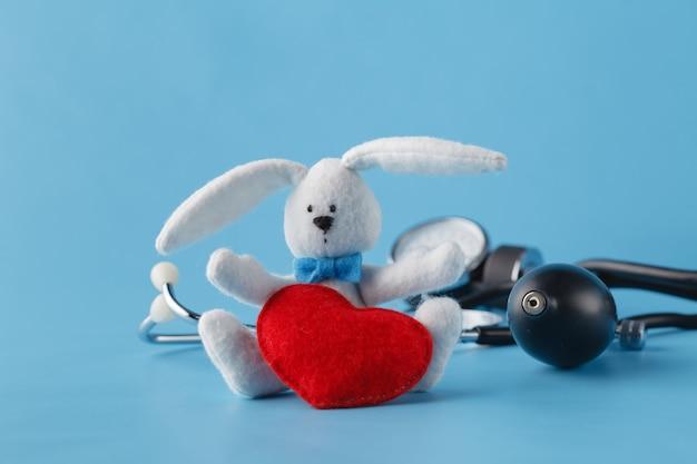Conceito de saúde do coração, tonômetro e coração de brinquedo em azul Foto Premium