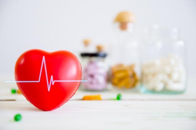 Conceito de saúde e médico. coração vermelho na mesa de madeira com conjunto de frascos de remédios e remédios Foto Premium