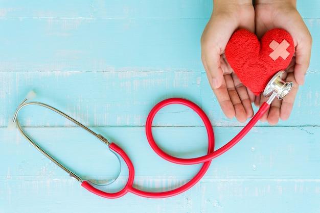Conceito de saúde e médico. mulher mão, segurando, vermelho, coração, com, estetoscópio Foto Premium