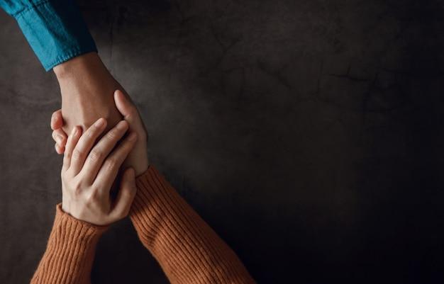 Conceito de saúde mental. casal fazendo toque de mão confortável para incentivar juntos. amor e cuidado. vista do topo Foto Premium