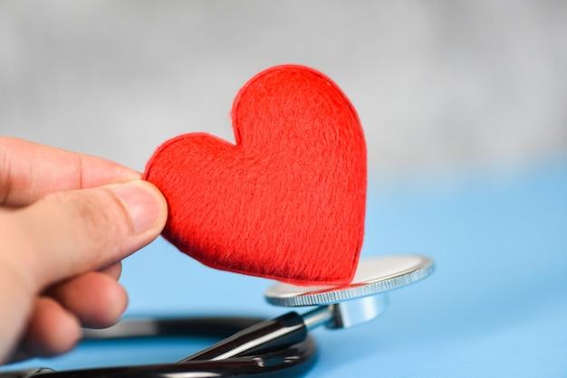 Conceito de saúde seguro - estetoscópio e cuidados de saúde coração vermelho sobre fundo azul Foto Premium