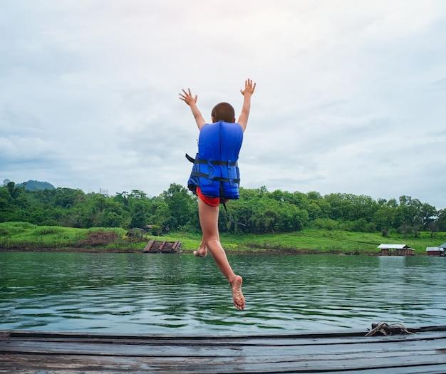 Conceito de segurança de vida. menino caucasiano usa um colete salva-vidas, pulando de madeira na água. Foto Premium
