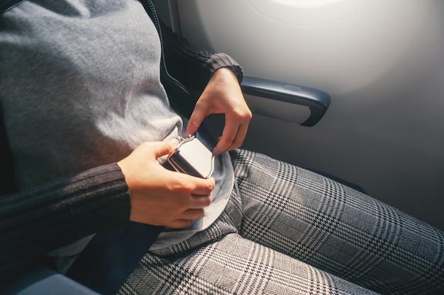 Conceito de segurança mulher asiática é cinto de fixação no avião pronto para decolar Foto Premium