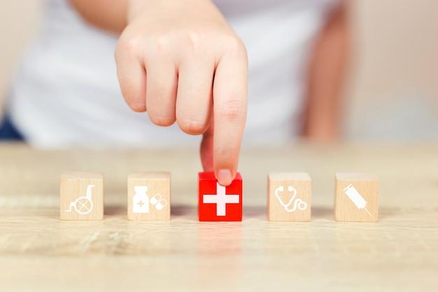 Conceito de seguro de saúde, mão organizando o empilhamento de bloco de madeira com médicos de cuidados de saúde de ícone Foto Premium