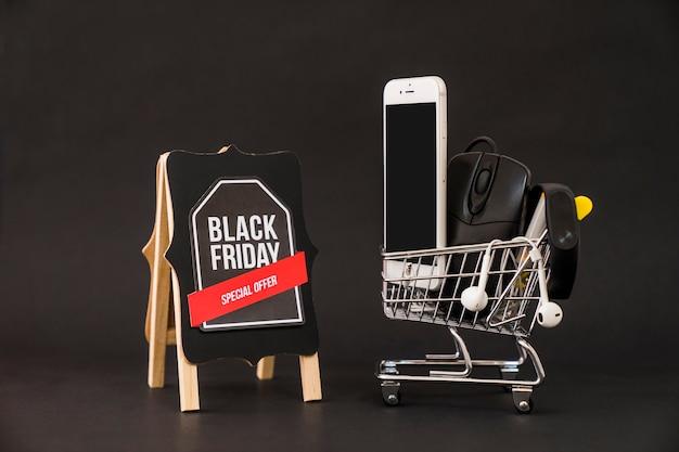 Conceito de sexta feira negra com smartphone no carrinho ao lado do tabuleiro Foto gratuita