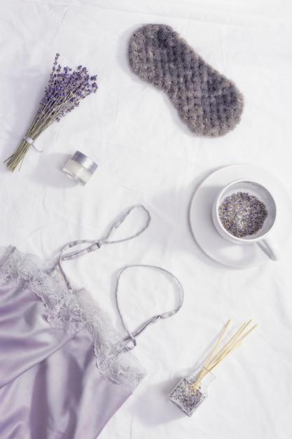 Conceito de sono noturno saudável, pijama de seda, máscara para dormir, xícara de chá de lavanda, aromas para adormecer melhor Foto Premium