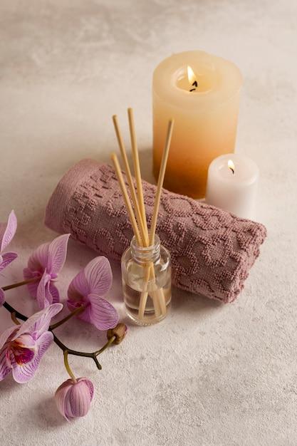 Conceito de spa de alto ângulo com velas e flores Foto gratuita
