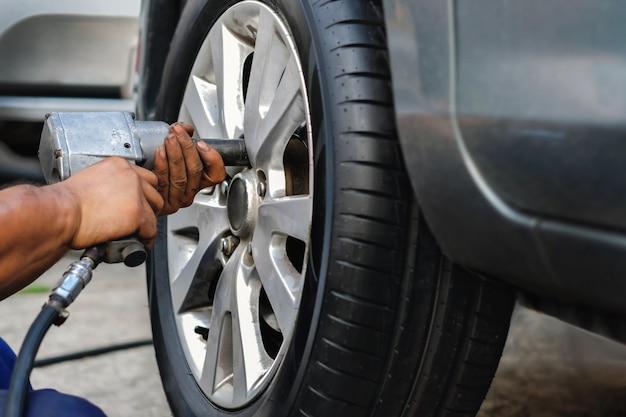 Conceito de substituição de pneus. mecânico using electric screwdriver wrench para porcas da roda na garagem. manutenção de carro e serviços Foto Premium