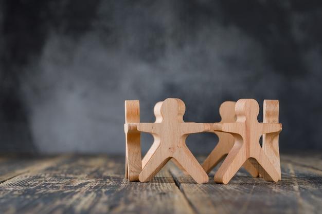 Conceito de sucesso comercial e trabalho em equipe com figuras de madeira da vista lateral dos povos. Foto gratuita