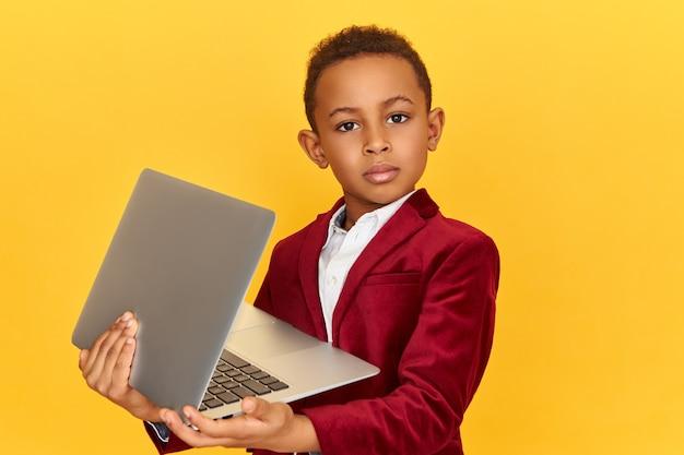 Conceito de tecnologia, dispositivos eletrônicos e dispositivos. imagem de estúdio de um garotinho confiante de pele escura posando isolado com um laptop nas mãos, usando uma conexão sem fio de alta velocidade à internet Foto gratuita