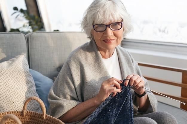 Conceito de tempo de lazer, hobby, relaxamento, idade e artesanato. mulher de meia-idade encantadora e alegre se aposentando, relaxando em casa, tricotando agasalho quente à venda, usando óculos elegantes e sorrindo Foto gratuita