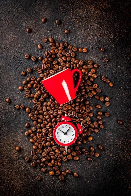Conceito de um começo alegre e bom para o dia, café da manhã. fundo enferrujado escuro com grãos de café, um despertador e uma xícara de café. espaço de cópia da vista superior Foto Premium
