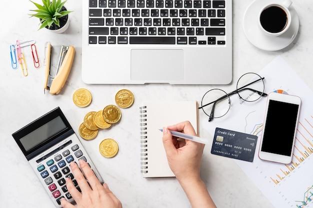 Conceito de uma mulher fazendo pagamento online com cartão e smartphone isolados em uma mesa de mármore moderna Foto Premium