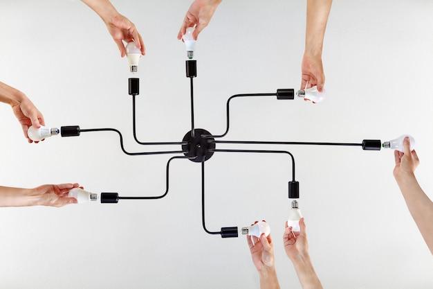 Conceito de valores compartilhados ou propósito compartilhado em exemplo de ações conjuntas durante o trabalho em equipe na substituição de lâmpadas led em iluminação de teto. Foto Premium