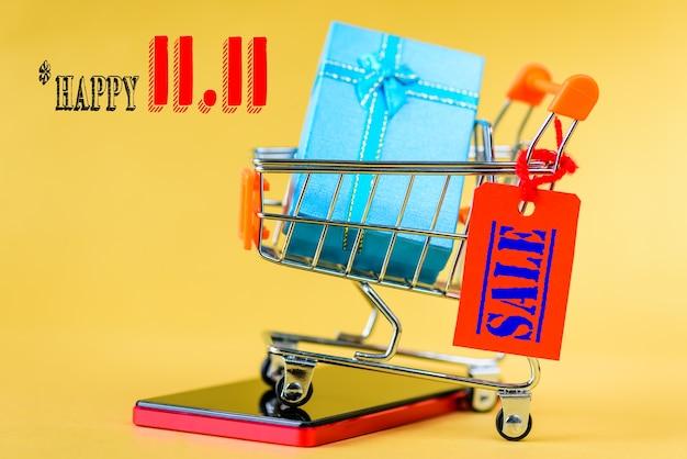 Conceito de venda de dia único chinês 11,11. carrinho de compras mini e caixa de presente com etiquetas. Foto Premium